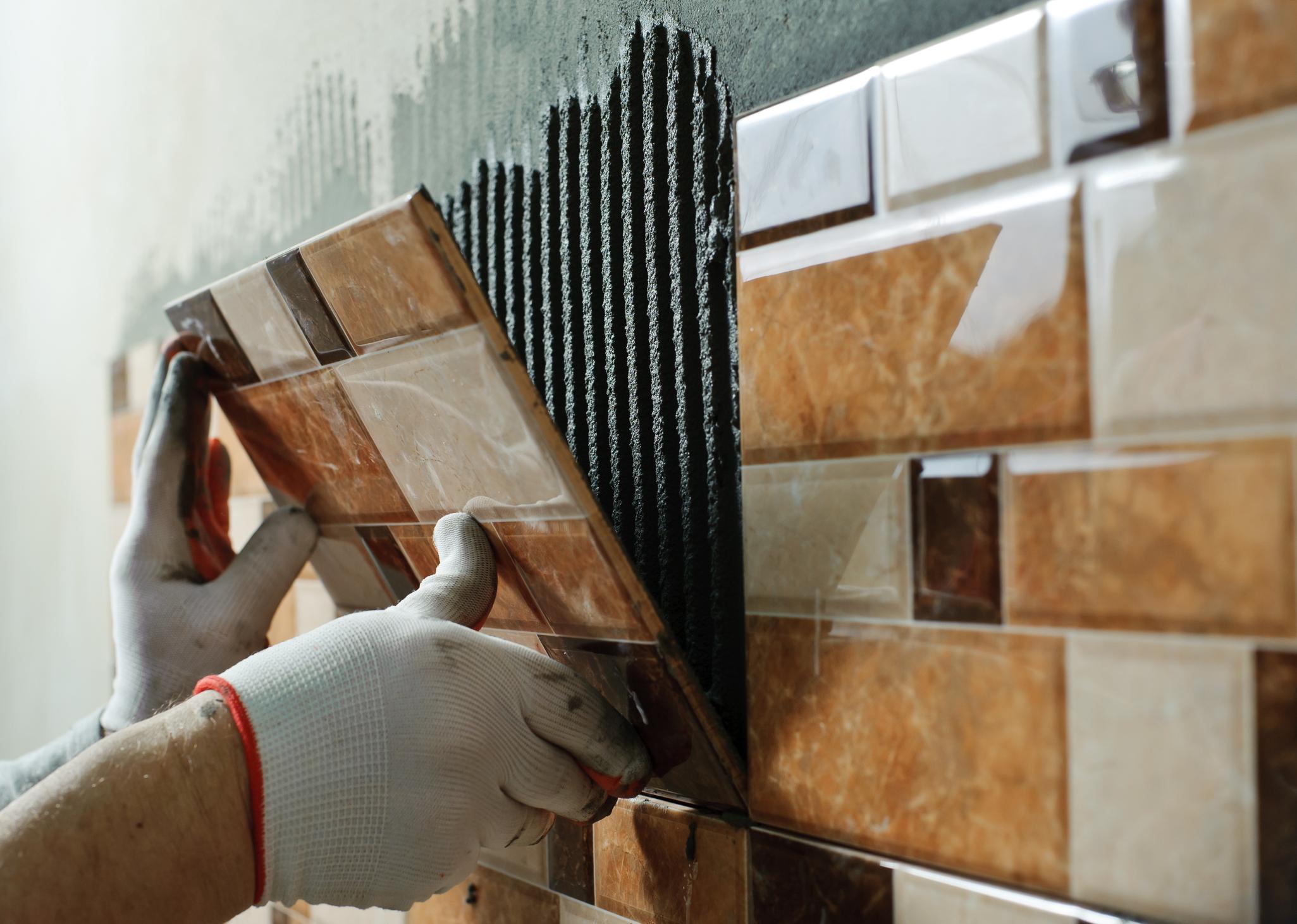 Pose de carrelage en céramique sur un mur